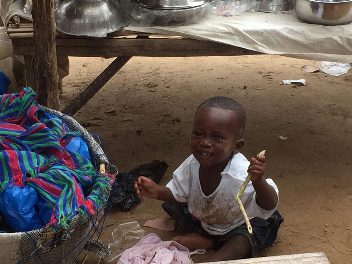 Ein kleiner Junge spielt am Marktstand seiner Mutter